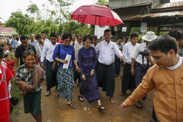 Лидер продемократии Мьянмы Аун Сан Су Чжи идет в деревне Вархейнха во время своих сквозных визитов просветительной избирательной кампании  в своем избирательном округе города Хохму, за пределами Янгона 4 июля 2015. Национальная демократическая лига Су Чжи (NLD), как ожидают, преуспеет на парламентских выборах, которые будут первым свободным и справедливым голосованием в Мьянме через 25 лет. NLD, у которого есть история бойкота, который он рассмотрел как испорченные политические процессы, вдохновленные прежней военной диктатурой, должен все же подтвердить, будет ли он лидировать на всеобщих выборах в ноябре. (REUTERS/Soe Бочка Зеи)