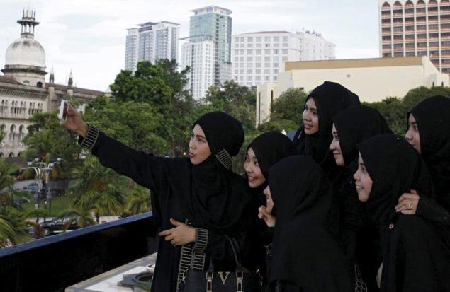 Женщины позируют для картины на национальной мечети во время Рамадана в Куала-Лумпуре, Малайзия, 4 июля, 2015 (REUTERS / Оливия Харрис)