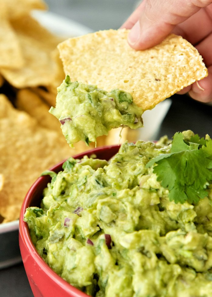 How to Make Homemade Guacamole - guacamole in a bowl wtih chips on the side