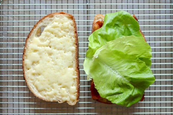 Two slices of bread with melted cheese on one and lettuce on the other