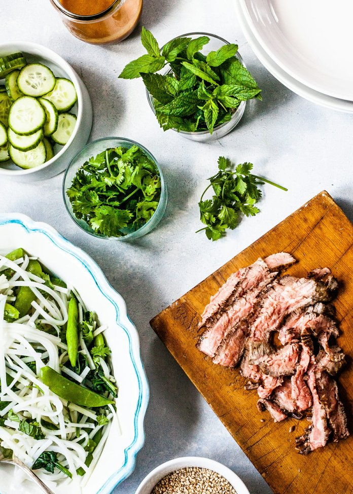 Noodles with Steak, Vegetables and Lime Dressing - sliced steak on cutting board with chopped vegetables nearby