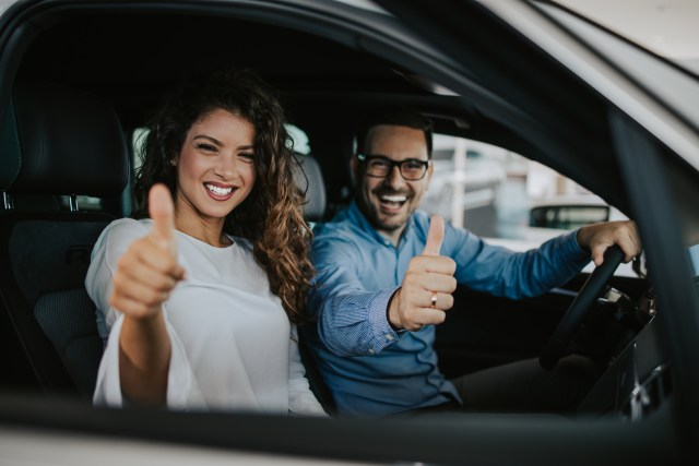 Attractive middle age couple buying car in showroom