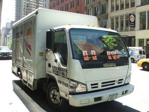 This image is a commercial vehicle with 5 parking tickets on its windshield