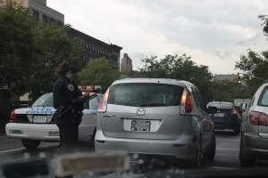 This is an image of a cop issuing a double parking ticket to a motorist in NYC