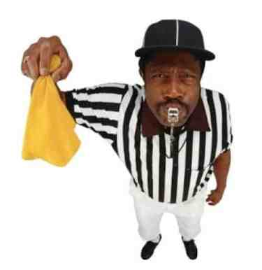 This image of a referred holding a yellow penalty flag signifies that there is a parking ticket penalty for parking an unaltered commercial vehicle