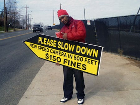 This image is a man warning motorists they are approaching a speed camera trap