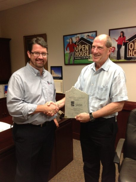 Andy Sevier from Paradigm Windows presents New York Sash owner Scot Hayes with a 10,000 Window Achievement Award.