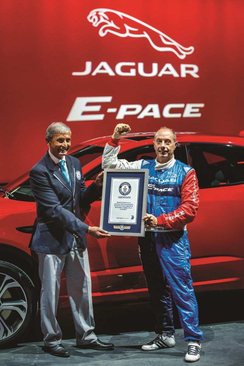 Jaguar stunt driver Terry Grant receives the Guinness World Record for longest barrel roll from adjudicator Pravin Patel at the global launch of the new Jaguar E-PACE at ExCel London.