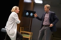 Kati Brazda as Dr. James and Steve Key as Dr. Sealey looking at CAT scans of two brains.