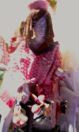 A copy of Taylor Mac's pink costume for 1956 to 1966, by Machine Dazzle, on display on a mannequin in the lobby of St. Ann's Warehouse