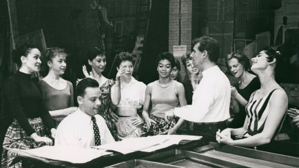 "Stephen Sondheim on piano and Leonard Bernstein standing amongst female singers rehearsing for ""West Side Story."""