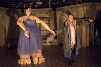 the ensemble of Mabou Mines' Glass Guignol fitting actress Maude Mitchell with gigantic arms and feet and turning her into a giant living puppet