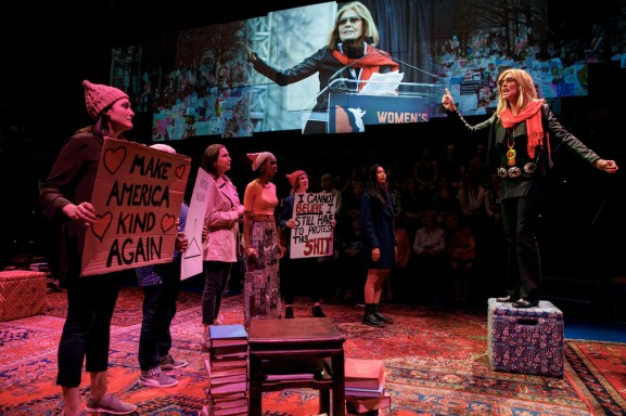 The cast as demonstrators, in front of a projection of the actual Gloria Steinem at a demonstration.