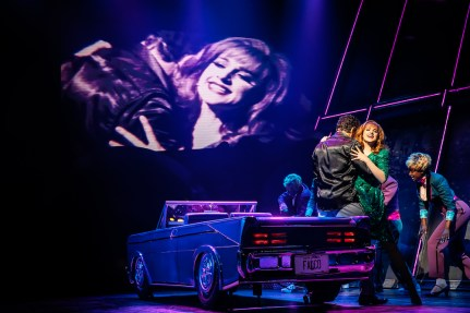 Lena Hall and Bradley Dean as Raven's parents embrace atop the convertible, remembering their steamy youth, their image capture on one of the many projects in Bat Out of Hell