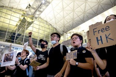 Protesters rally against a controversial extradition bill in the arrivals hall of the international airport , singing a song from a Broadway musical