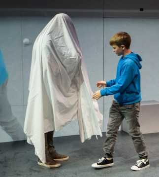 Aran Murphy with a member of the audience, whom he's covered with a sheet in order to portray the ghost of Hamlet's father.