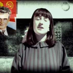 Mica Hastings as Flavia, the teacher who spouts dictator propaganda in her classroom
