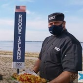 "Rhode Island, masked chef holds Calamari while a state representative points out ""our state appetizer, calamari, is available in all 50 states."""