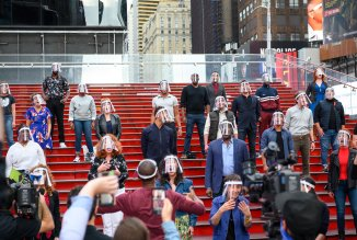 Bernadette Peters et al singing on the red steps of Times Square