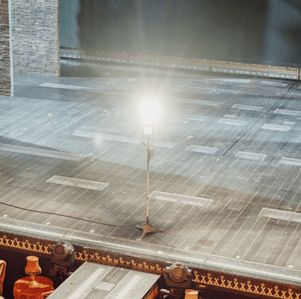 the ghost light remains lit on the stage of the Al Hirschfeld Theater