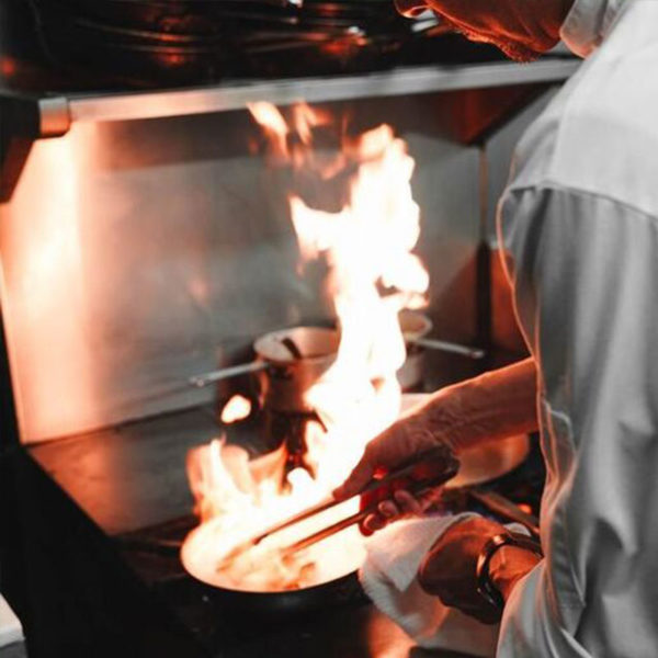 A chef cooks over an open flame.