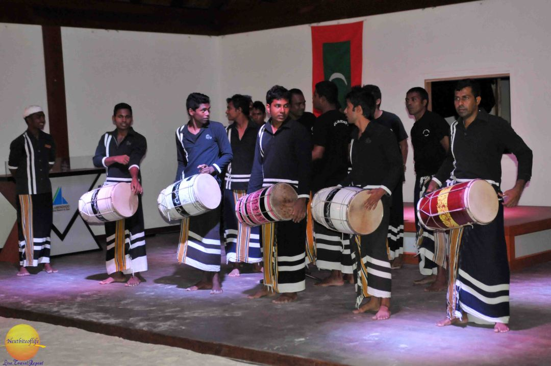 Maldivian men in traditional outfit drumming and singing.