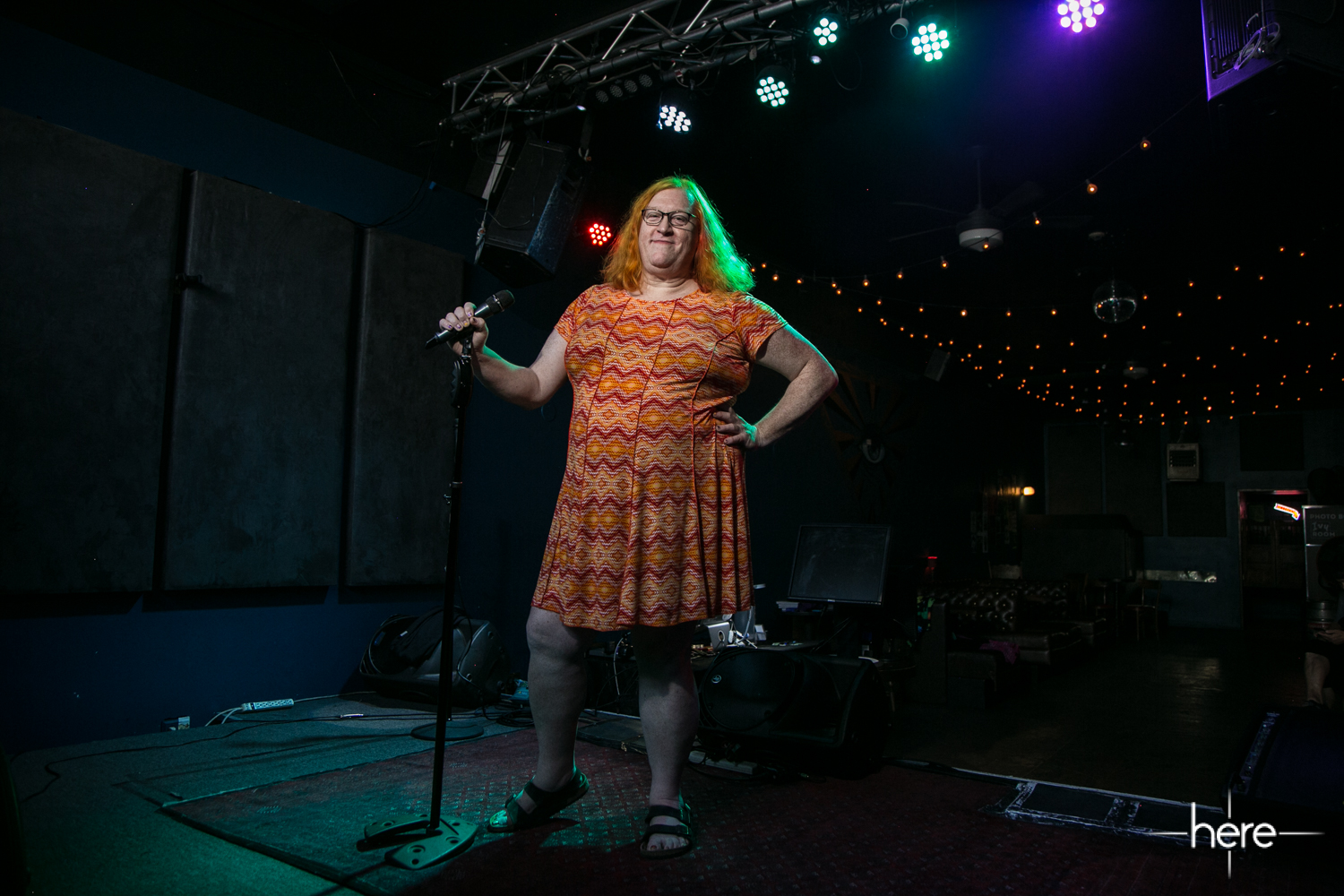 Dana Morrigan on a stage in an orange dress, holding a mic on a stand, her hair illuminated green by the stage lights.