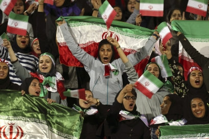 Iranian women cheer as they wave their country's flag after authorities in a rare move allowed a select group of women into Azadi stadium to watch a friendly soccer match between Iran and Bolivia, in Tehran, Iran, Oct. 16, 2018.