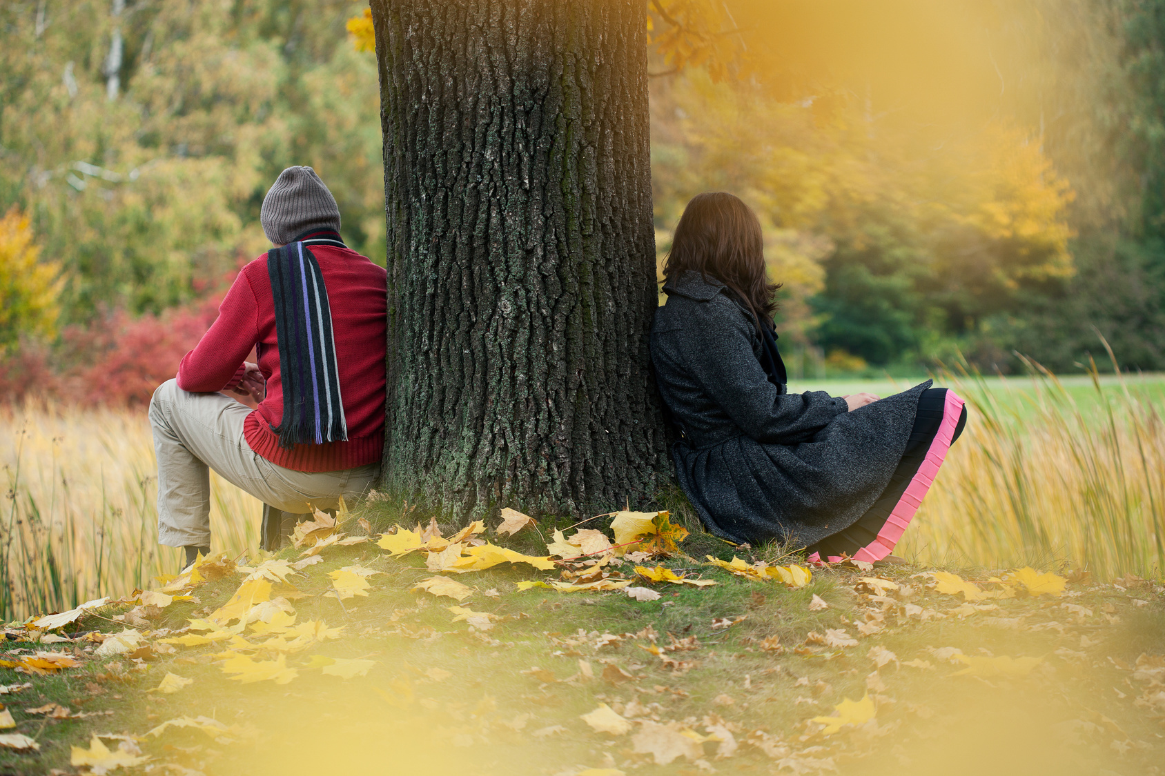 Man and woman contemplating, sat leaning on tree.