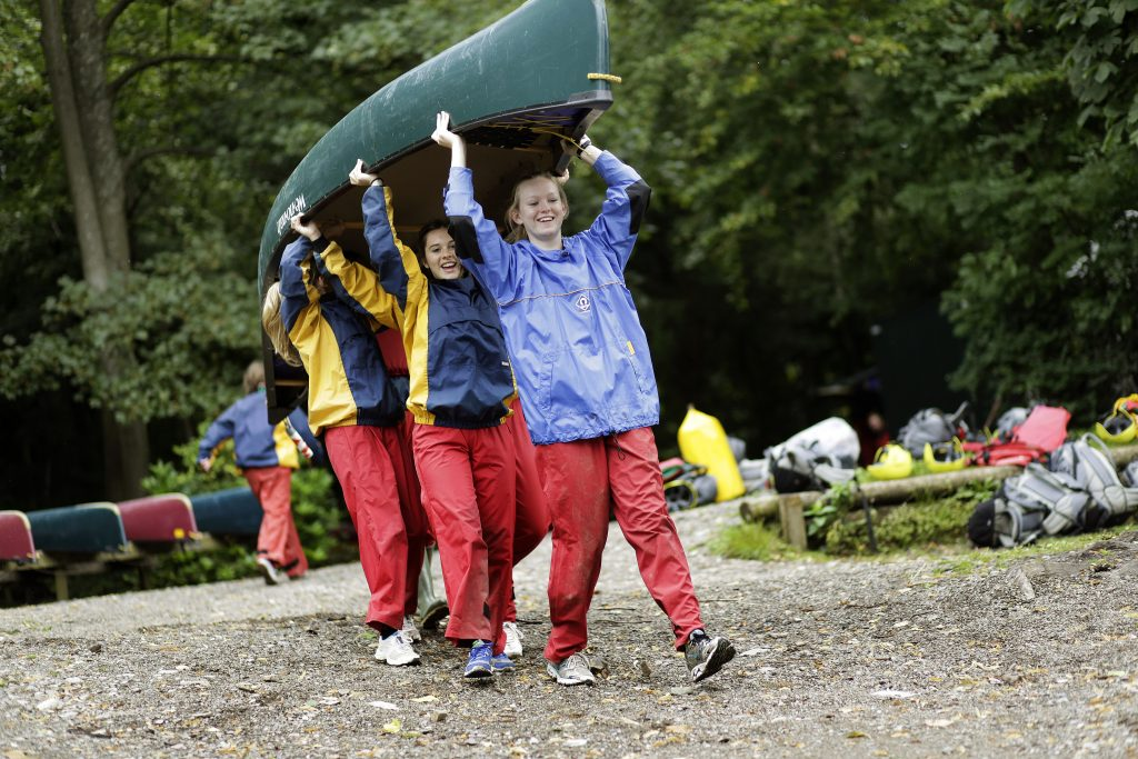 Girls carrying a canoe over their heads.