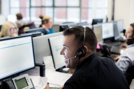 Man smiling while working in call centre.