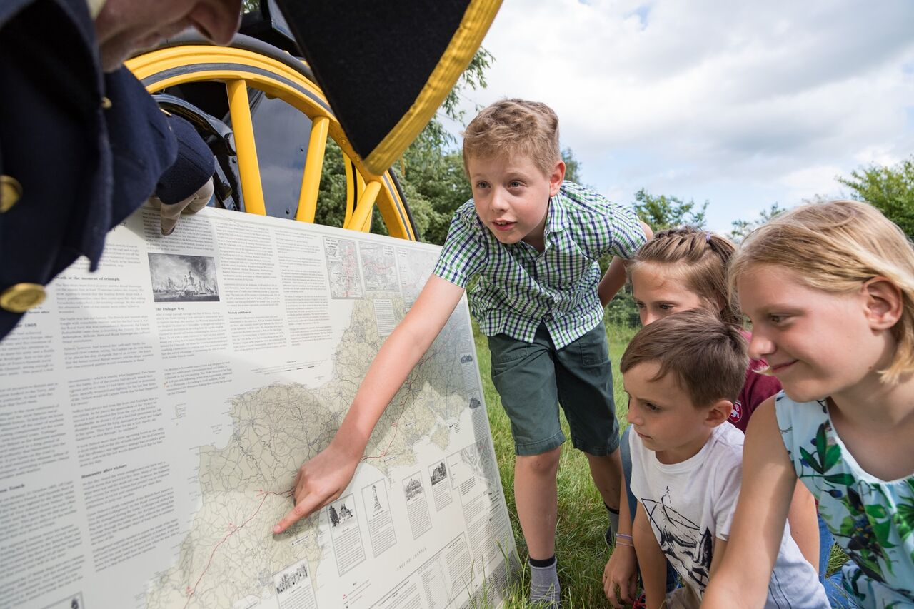 Children reading and pointing at a map and informational posters