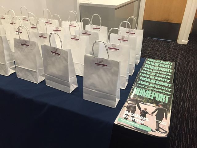 Table full of goodie bags and copies of Homeport magazine.