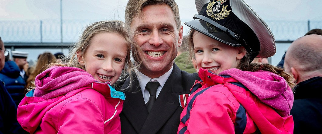 Father reunited with children, one of which is wearing his hat.