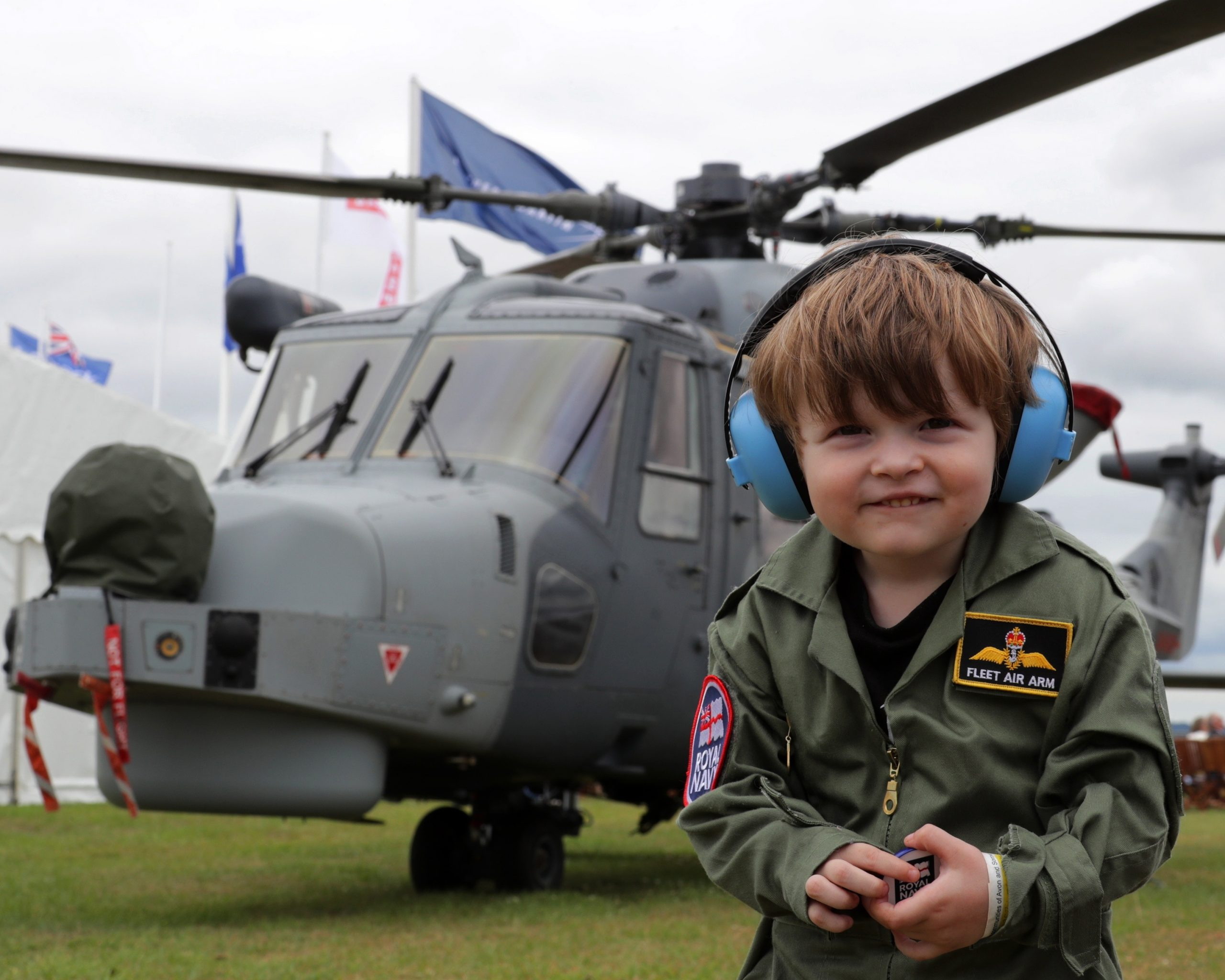 Boy in fleet air arm overalls and earmuffs with helicopter behind him.