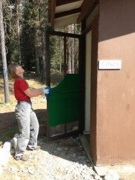 Margaret cleaning the women's outhouse