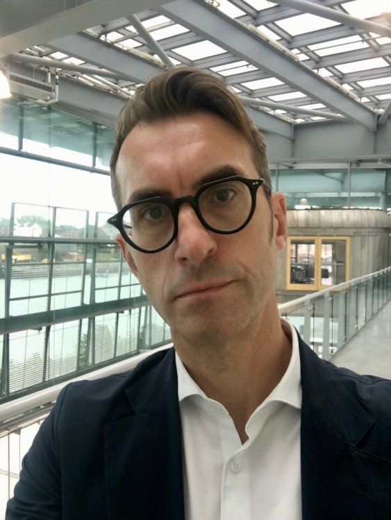 Head and shoulders image of a white male in his 40s with short brown hair and black rimmed glasses, wearing a white shirt and black blazer on the indoor balcony of a glass and grey metal building.