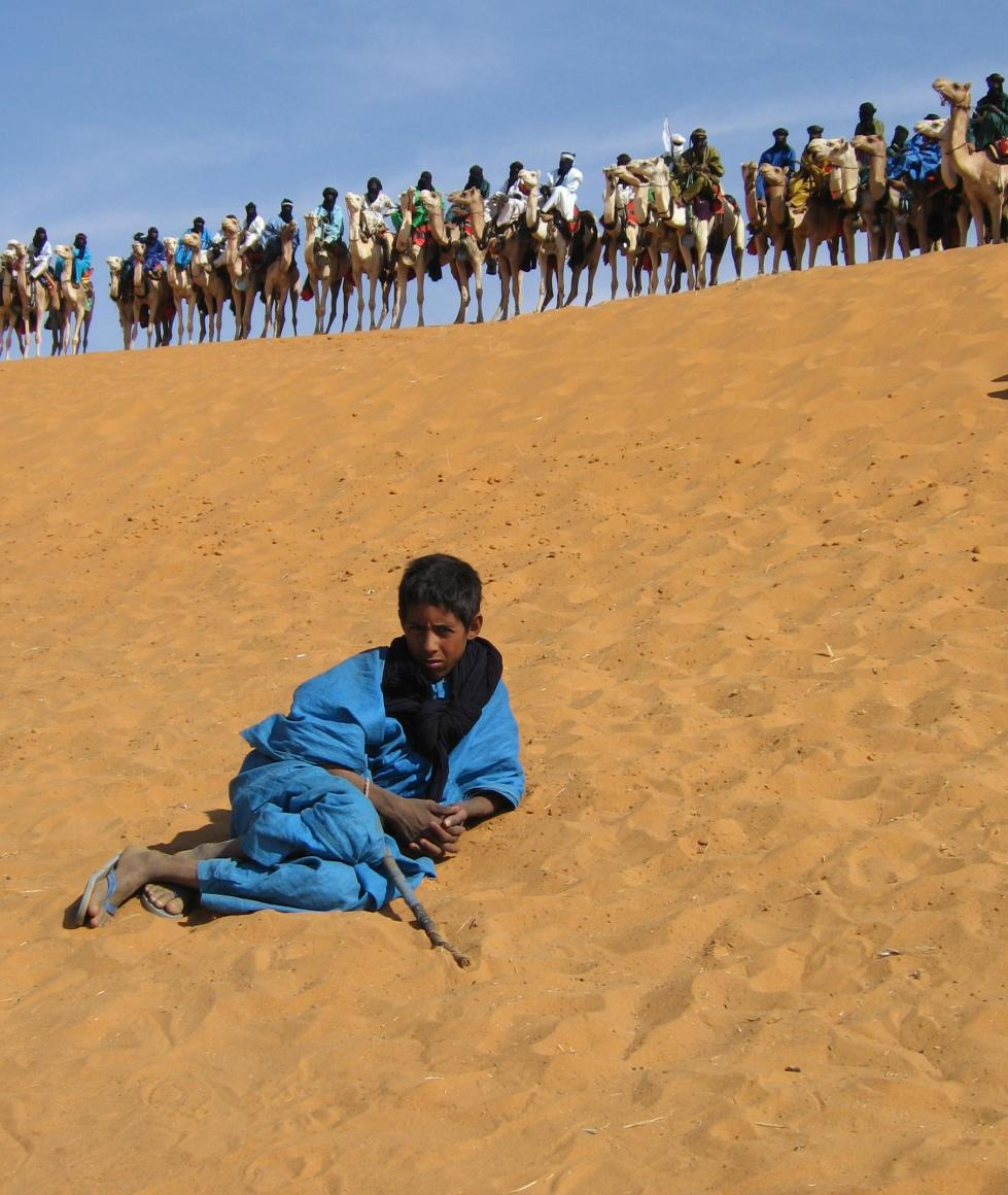 boy in blue with camels behind