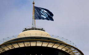 Bandeira com novo logo do Seattle Kraken sobre Space Needle