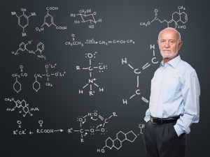 Photo of an older man standing in front of a blackboard.