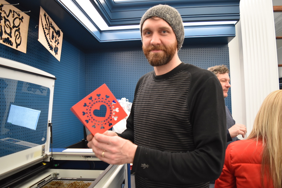 man in grey hat with beard displaying red card with hearts cut out of it