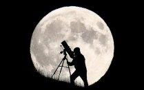 Một nhà thiên văn học in bóng phía trước mặt trăng khi ông chuẩn bị chiêm ngưỡng hiện tượng này ở Brighton. Ảnh: Jordan Mansfield/Getty