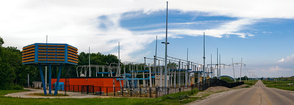 A panorama showcasing Wilsons blue-and-orange color scheme and his self-designed π-shaped power poles stretching off into the distance.