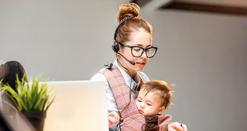Woman working with baby in sling