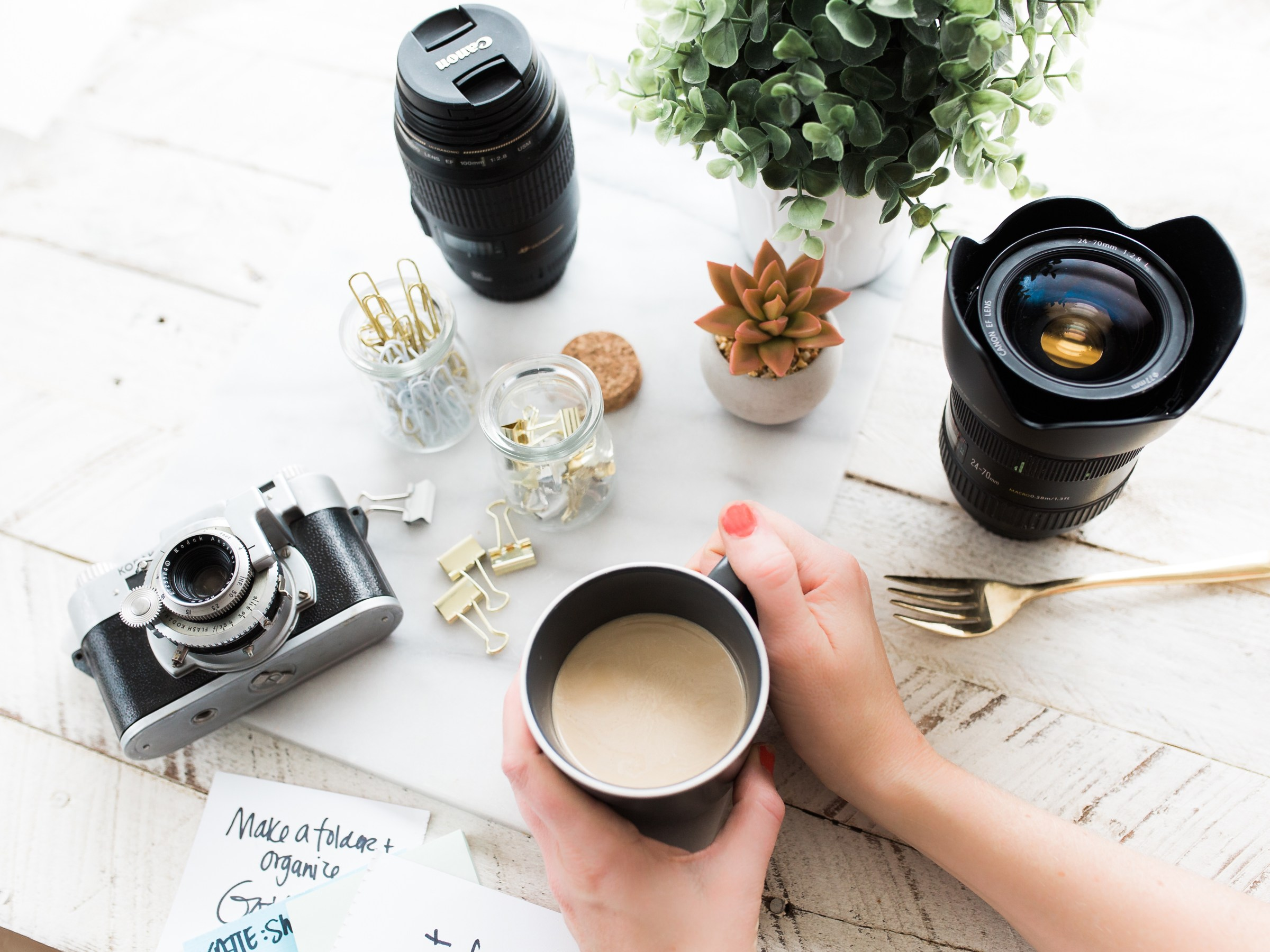 Unsplash picture of woman holding a cup of coffee at a desk