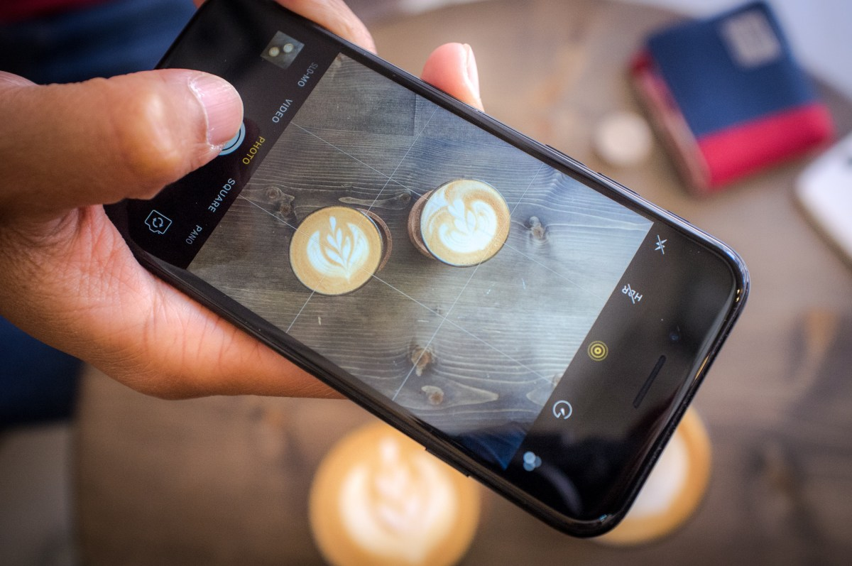 Person taking picture of coffee using an iphone