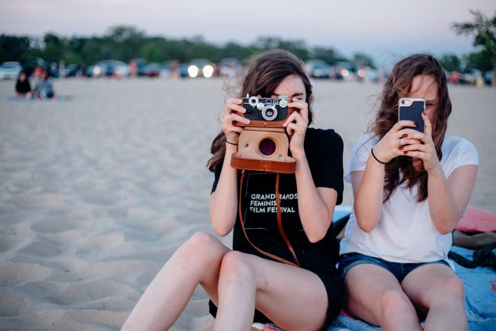 Picture of two girls taking photographs in the sand