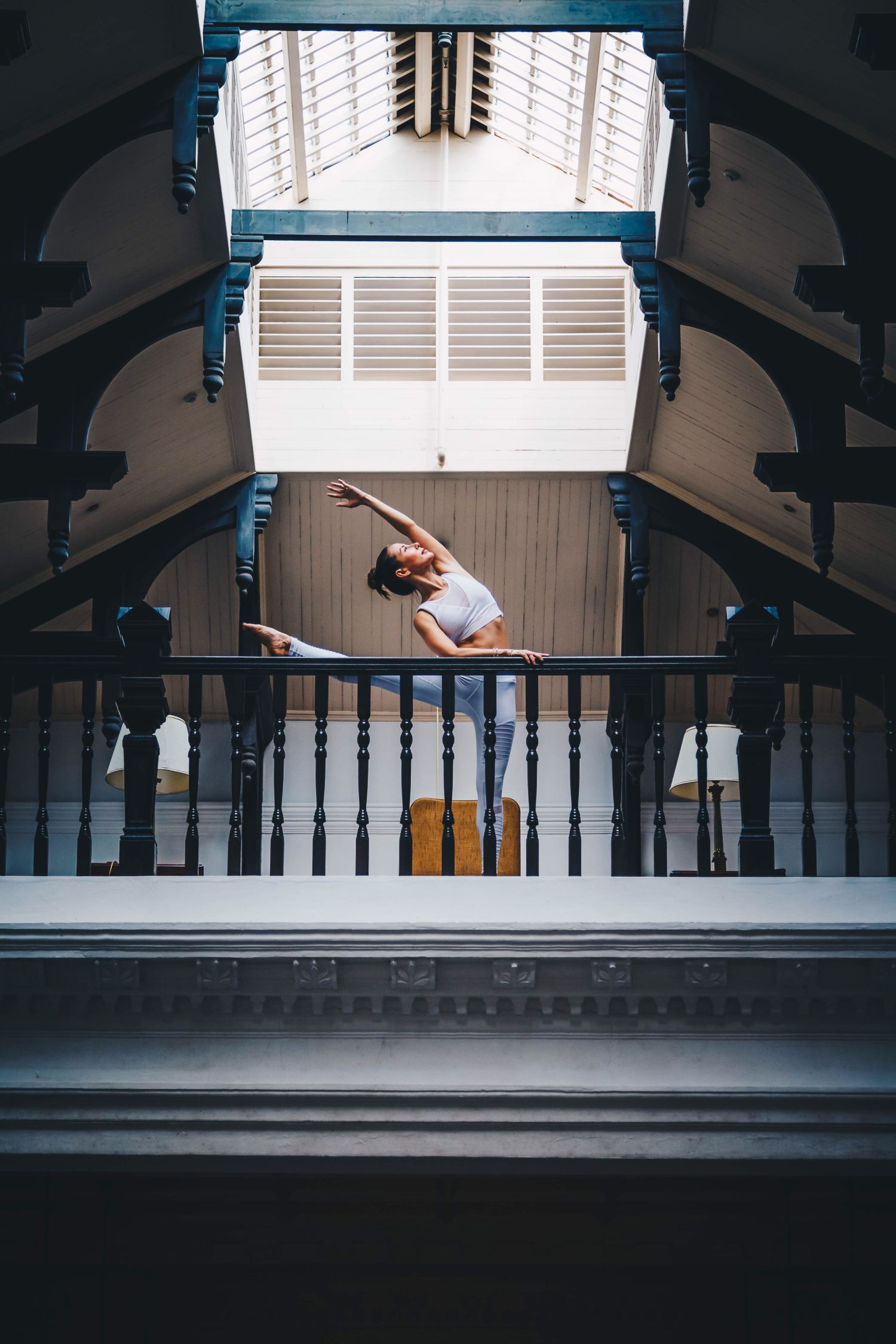 Portrait of a woman stretching on a balcony at Raffles Hotel