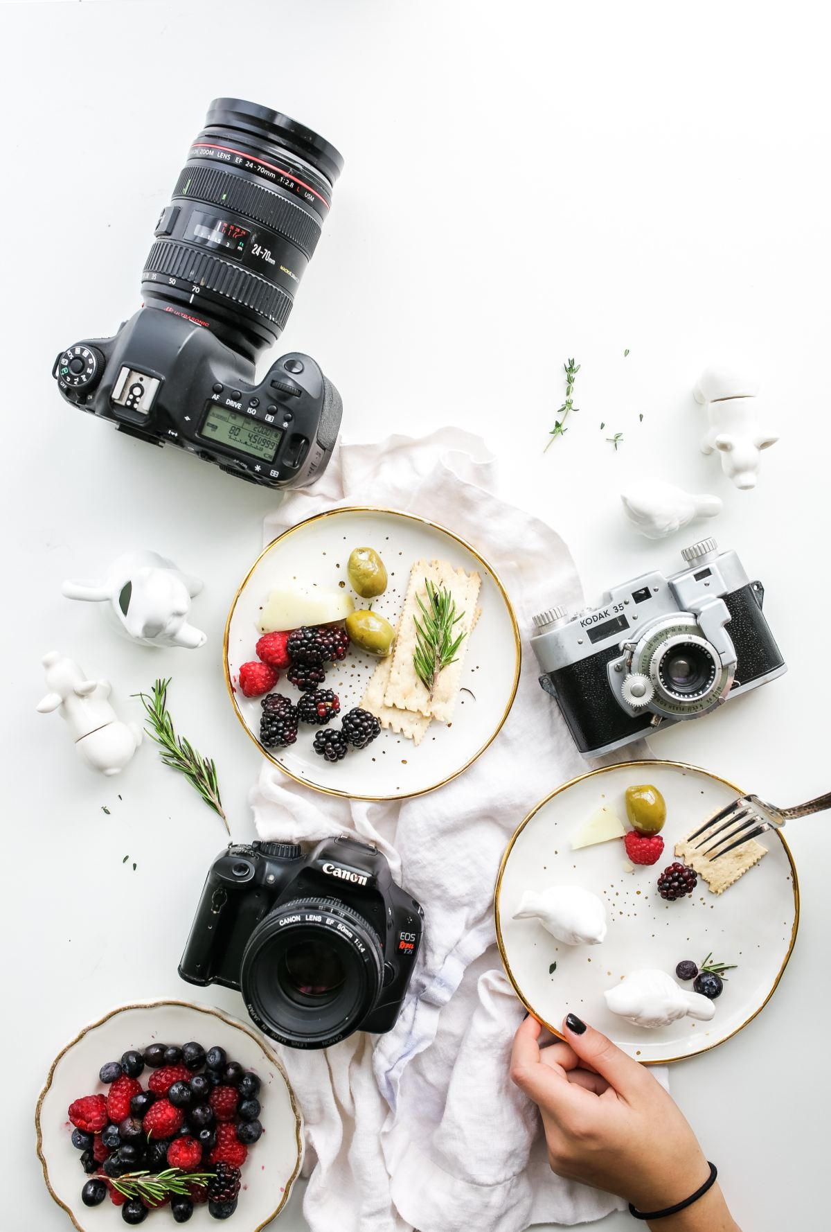 Picture of three cameras on a restaurant table with plates of food