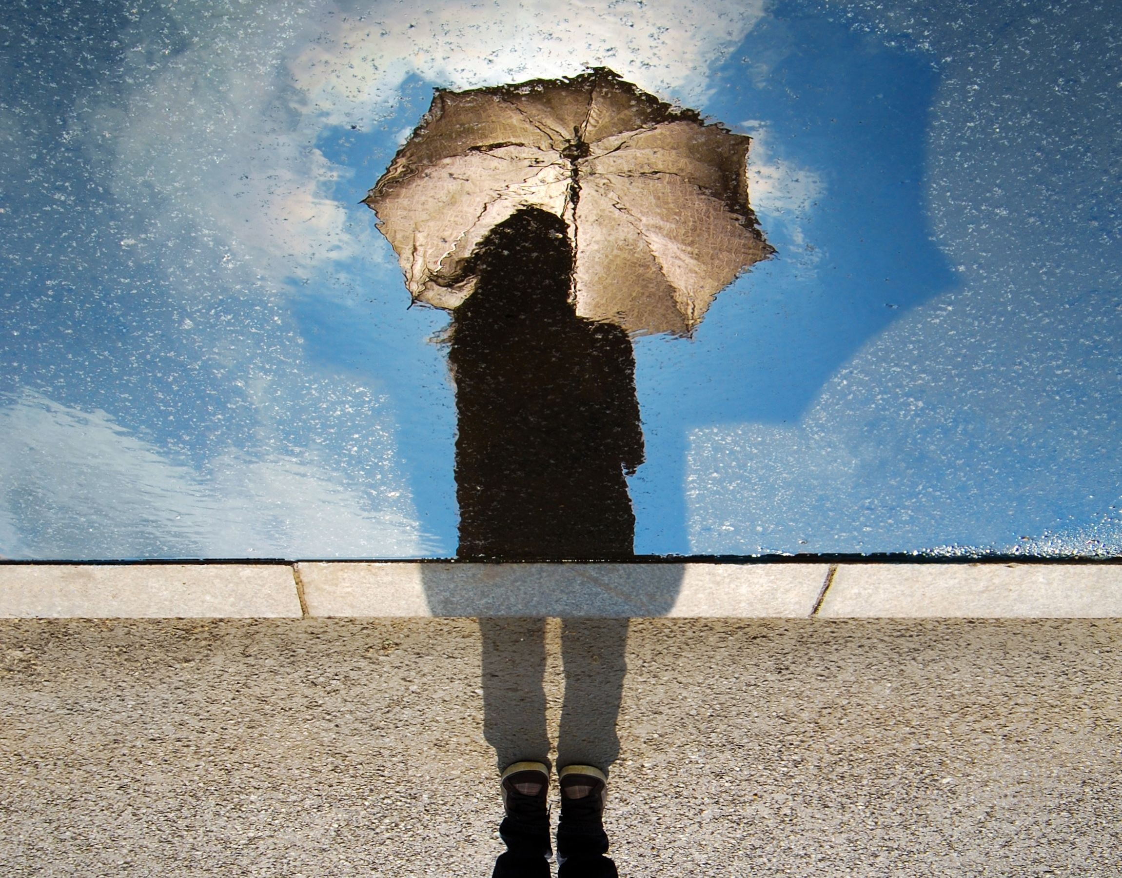 Woman with reflection in water holding an umbrella in the rain and wind